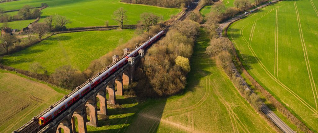 Train going over viaduct in countryside