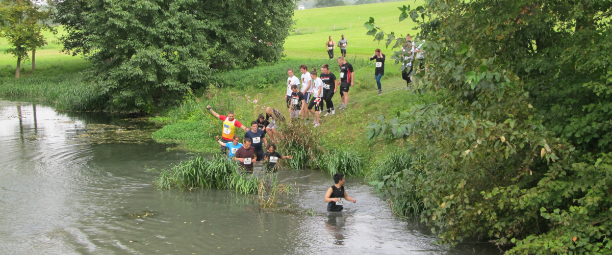 Event venue in countryside with runners entering river